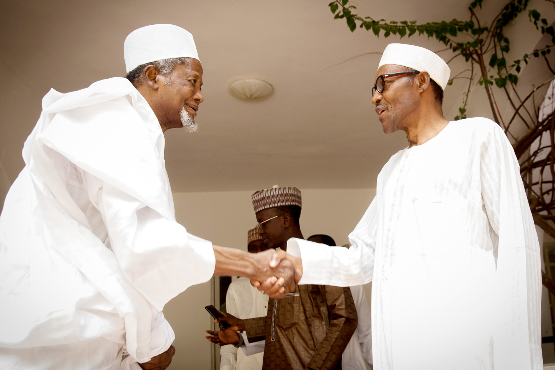 Aminu Dantata shakes hands with then President Elect, General Muhammadu Buhari in Daura, Katsina State. (Photo Credit; Sunday Aghaeze)